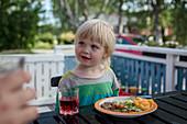 Kleines Mädchen sitzt am Tisch beim Essen