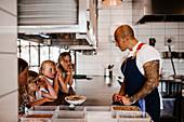 Girls watching chef working in restaurant kitchen