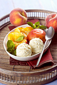 Peach ice cream served with poached peaches