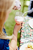 Mädchen gießt Getränk in Weinglas