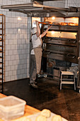 Female baker taking bread out of oven