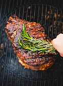 Flavouring beef chops with rosemary on a grill