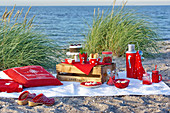 Picnic with red dishes on the beach