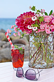A table at the beach with a bouquet of roses, dahlia, and phlox, and a cocktail