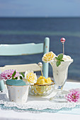 Vanilla ice cream in cups decorated with rose blossoms, in the background pieces of pineapple in a bowl