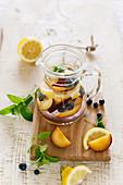 Detox water with blueberries, peach, lemon, lemon balm and mint