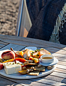 An outdoor table with a cheeseboard with feta, parmesan, crackers, pistachios, peaches, thyme and honey