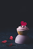 Valentine's Day cupcake with pink frosting and heart decoration
