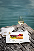 Char dish and a glass of white wine, served on a wooden table with a view of a lake