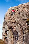 Rock climber on a crag, Scotland, UK