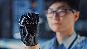 Prosthetic robot arm being tested by an engineer