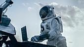 Astronaut using a laptop on an alien planet