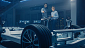 Engineers working on an electric car chassis prototype