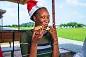 Woman eating dessert in a Santa hat