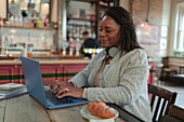 Woman working on a laptop in a cafe
