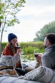 Couple drinking wine on patio cushions