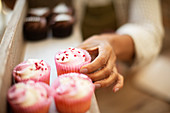 Hand reaching for pink cupcake