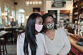 Mother and daughter in face masks in a pub