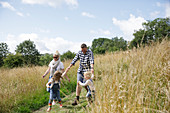 Happy family running in a sunny rural field