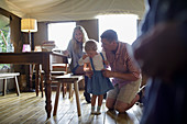 Happy family at dining table in yurt cabin