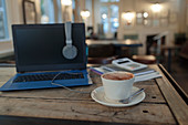 Cappuccino on table next to laptop in cafe