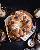 A sesame Challah bread wreath on a round wood board, with flour, seasalt and butter