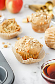 A partially unwrapped apple and oat muffin on a light background