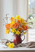 Frühlingsstrauß aus Tulpen, Narzissen und Zweigen der Felsenbirne