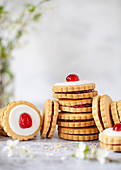 Jam filled shortbread cookies stack up, some with glaces icing and a cherry on the top to form Empire Biscuits