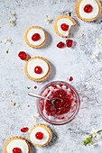 A line of jam filled shortbread biscuits topped with glace icing and cherries alongside a bowl of jam