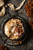 A single-serve cast iron skillet holding pear and chocolate crumble topped with cream