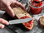 Strawberry-rhubarb jam being spread on bread