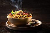 Tunisian couscous dish with vegetables against a dark background