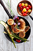 Grilled chicken and vegetables on white wooden table