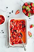 Obstsalat mit Erdbeern, Heidelbeeren, Zitrone und Zucker
