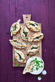Mini pide (flatbread) with spinach filling and yogurt herb dip