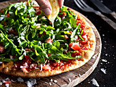 Arugula Pizza with lemon being squeezed over it