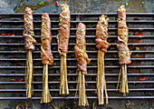 Marinated beef slices on lemongrass skewers on grill