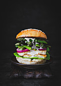 Burger mit Halloumi-Käse, gegrilltem Spargel und eingelegten Zwiebeln