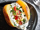 Grilled potatoes with tomato, herbs, and sour cream