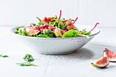 Wild herb salad with pomegranate seeds and figs