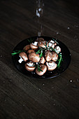 Sea salt and rosemary on button mushrooms in a bowl