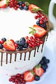 White drip cake with fresh berries