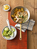 Pan fried fish with fried potatoes and cucumber salad
