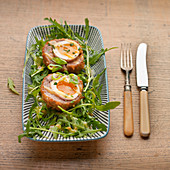 Two Scotch eggs with runny yokes on rocket salad