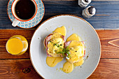 Eggs Benedict zum Frühstück mit Schinken und Sauce Hollandaise