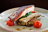 Pan fried salmon steak on potato rosti and spinach with cherry tomatoes