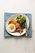 Potato pancakes with a fried egg and prosciutto