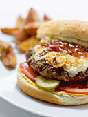Lemmy burger made of ground steak with bacon with caramelized whiskey onions, and cheese and served with steak fries