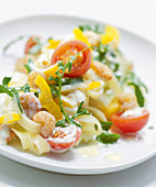 Tagliatelle tossed in a creamy cheese sauce with shrimp, yellow peppers, cherry tomatoes, and arugula